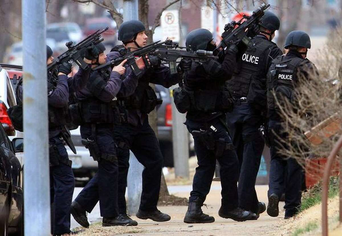 A St. Louis police tactical team enters a house in the 3100 block of Osage on Tuesday after a gunman reportedly shot two U.S. marshals and a St. Louis police officer, in St. Louis. A suspect later died.(AP Photo/St. Louis Post-Dispatch, Christian Gooden)