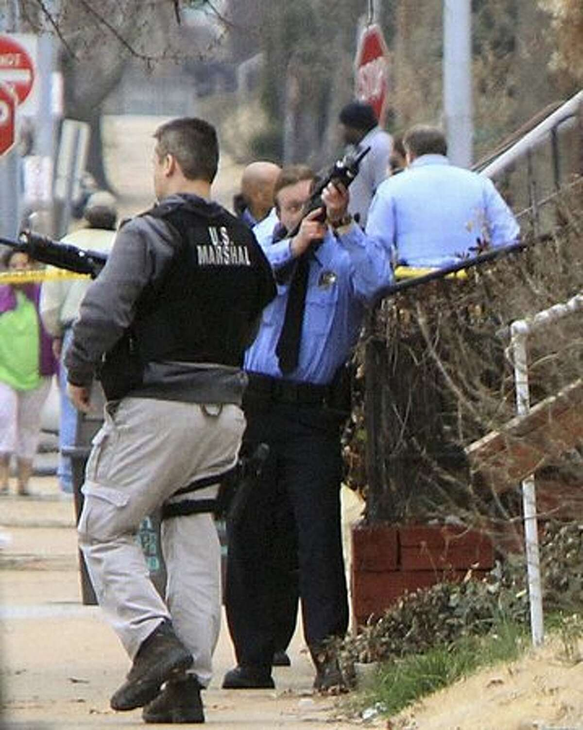 St. Louis police search for a gunman Tuesday in St. Louis. St. Louis police say two federal marshals and a police officer wered shot during a gunfight that left another man dead at a home. (AP Photo/St. Louis Post-Dispatch, Christian Gooden)