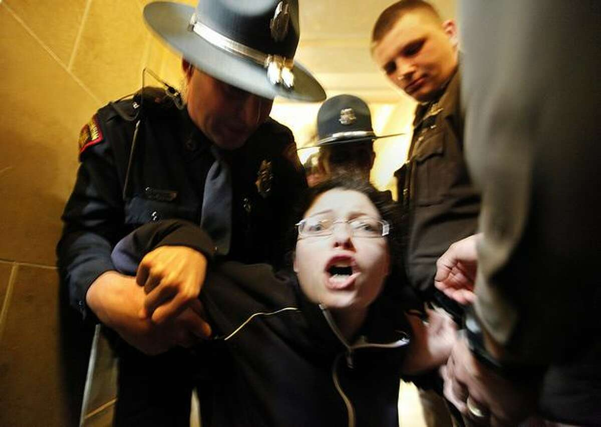 Elizabeth Wrigley-Field of Madison, Wis. is escorted out of the Wisconsin State Capitol Assembly Room lobby on Thursday in Madison, by law enforcement personnel after spending the night in the room with demonstrators opposed to Gov. Scott Walker's budget repair bill. Tensions have flared after Republican senators passed an amended version of the controversial bill which largely strips collective bargaining for public employees. (AP Photo/Wisconsin State Journal, John Hart)