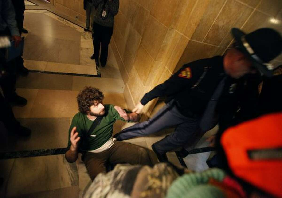Owen Curtis is escorted out of the Wisconsin State Capitol Assembly Room lobby by law enforcement personnel on Thursday after spending the night in the room with demonstrators opposed to Gov. Scott Walker's budget repair bill, in Madison, Wis. Tensions have flared after Republican senators passed an amended version of the controversial bill which largely strips collective bargaining for public employees. (AP Photo/Wisconsin State Journal, John Hart)