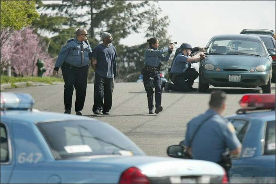 Seattle Police officers detain a man, one of about 7 people, after the responding to call of shots fired at house on S. Snoqualmie St., just east of S. Columbian Way, on Beacon Hill in Seattle on Wednesday. Photo: Dan DeLong, Seattle Post-Intelligencer / Seattle Post-Intelligencer