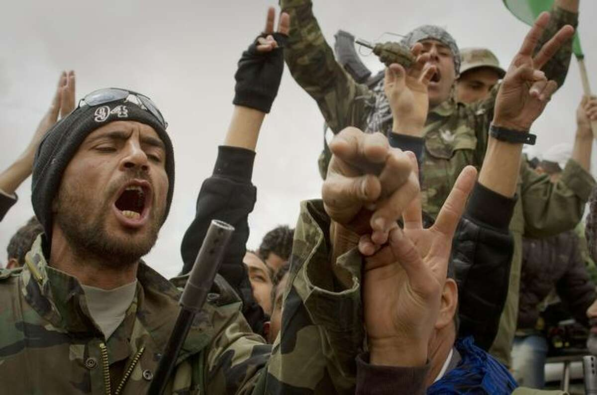 Libyan rebels react on outskirts of the city of Ajdabiya, south of Benghazi, eastern Libya, Monday, March 21, 2011. The international military intervention in Libya is likely to last