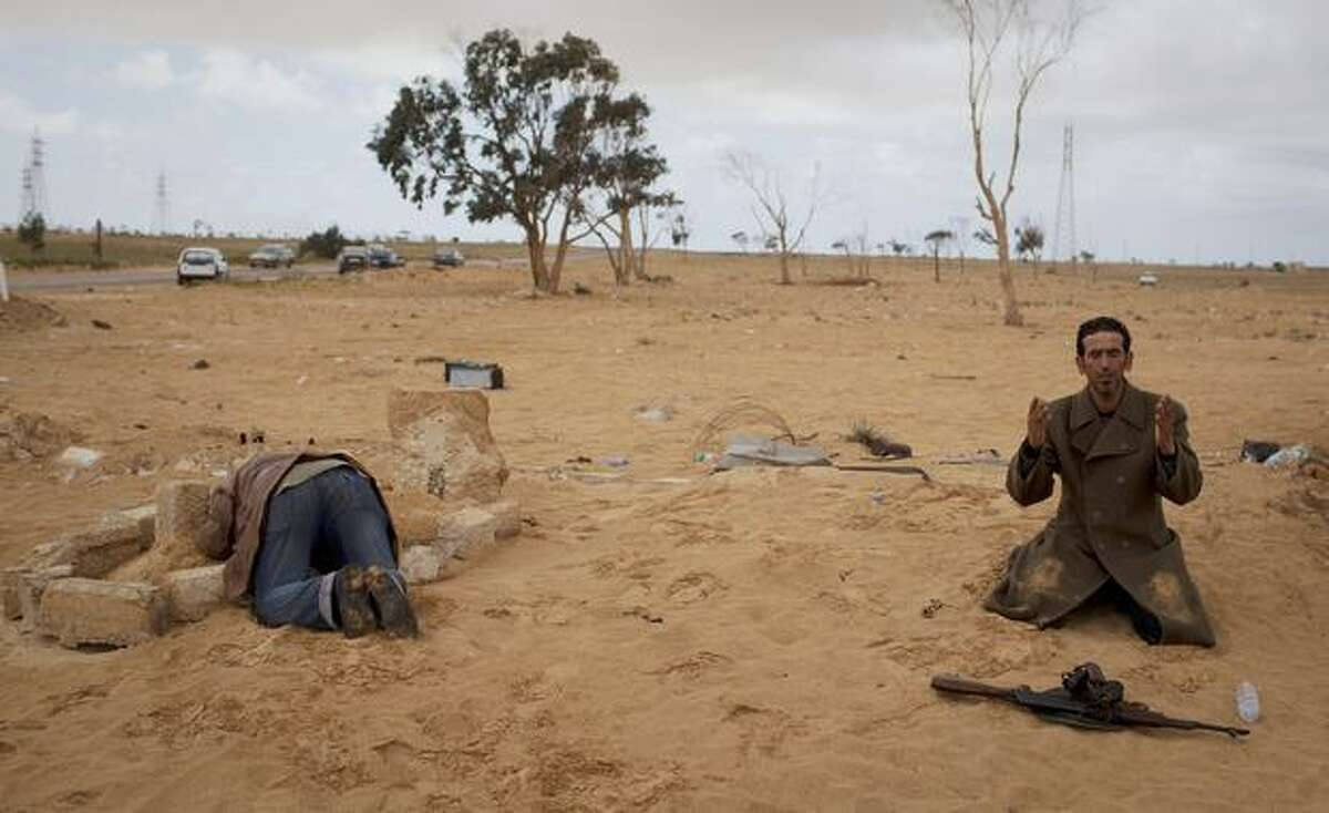 A Libyan rebel prays next to his gun while another one kneels over the grave of his dead brother, killed in the fighting, on the outskirts of Ajdabiya, south of Benghazi, in eastern Libya, on Monday, March 21, 2011. The international military intervention in Libya is likely to last