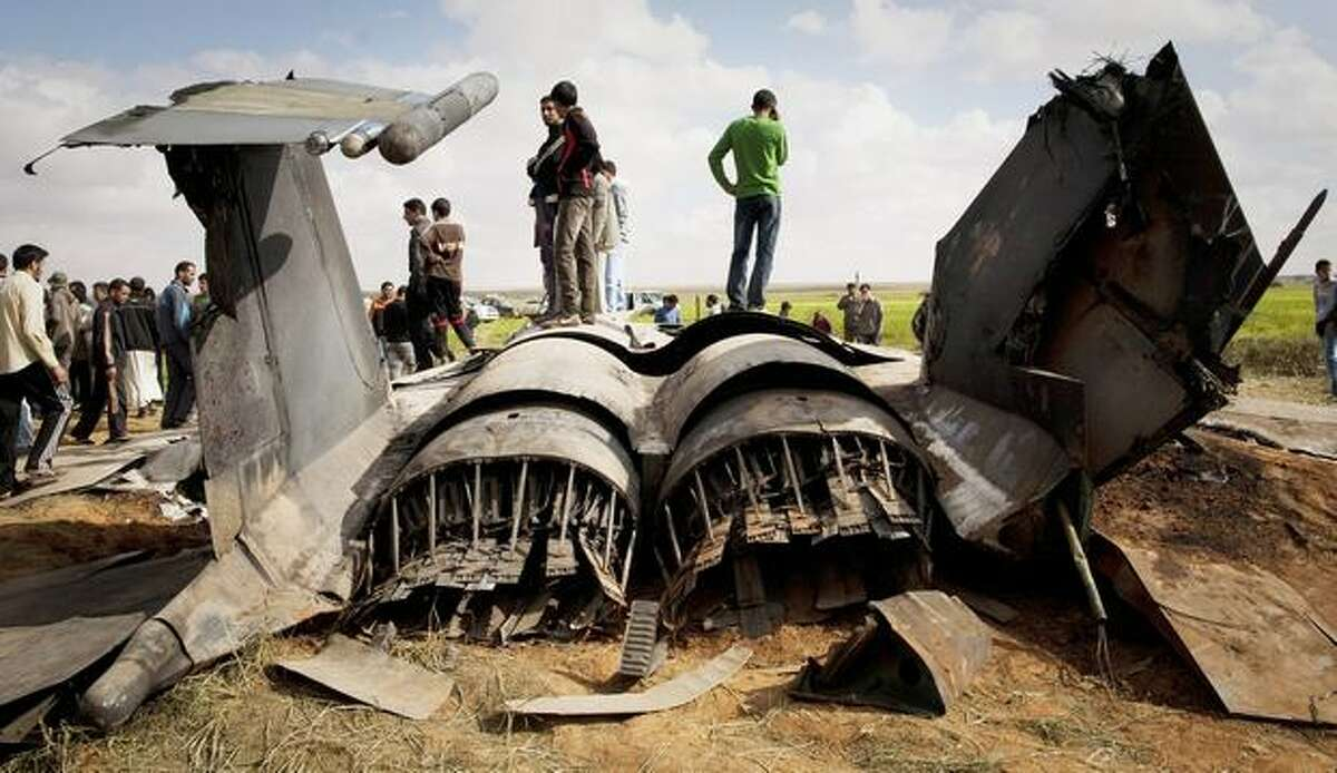 Libyans inspect the wreckage of a U.S. F-15 fighter jet after it crashed in an open field in the village of Bu Mariem, east of Benghazi, eastern Libya, Tuesday, March 22, 2011, with both crew ejecting safely. The U.S. Africa Command said both crew members were safe after what was believed to be a mechanical failure of the Air Force F-15. The aircraft, based out of Royal Air Force Lakenheath, England, was flying out of Italy's Aviano Air Base in support of Operation Odyssey Dawn.(AP Photo/Anja Niedringhaus)