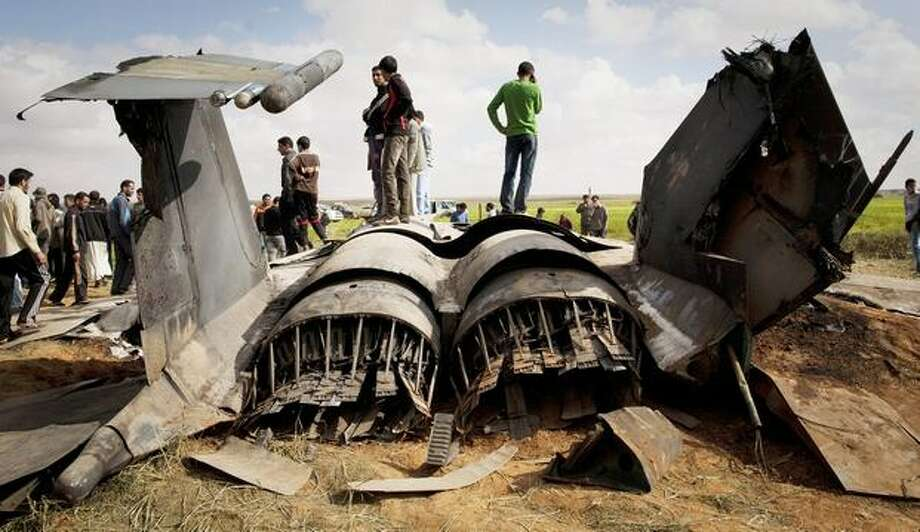 Libyans inspect the wreckage of a U.S. F-15 fighter jet after it crashed in an open field in the village of Bu Mariem, east of Benghazi, eastern Libya, Tuesday, March 22, 2011, with both crew ejecting safely. The U.S. Africa Command said both crew members were safe after what was believed to be a mechanical failure of the Air Force F-15. The aircraft, based out of Royal Air Force Lakenheath, England, was flying out of Italy's Aviano Air Base in support of Operation Odyssey Dawn.(AP Photo/Anja Niedringhaus) Photo: Associated Press / Associated Press