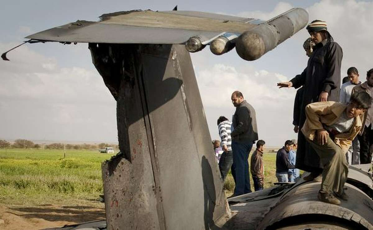 Libyans inspect the wreckage of a U.S. F-15 fighter jet after it crashed in an open field in the village of Bu Mariem, east of Benghazi, eastern Libya, Tuesday with both crew ejecting safely. The U.S. Africa Command said both crew members were safe after what was believed to be a mechanical failure of the Air Force F-15. The aircraft, based out of Royal Air Force Lakenheath, England, was flying out of Italy's Aviano Air Base in support of Operation Odyssey Dawn.(AP Photo/Anja Niedringhaus)