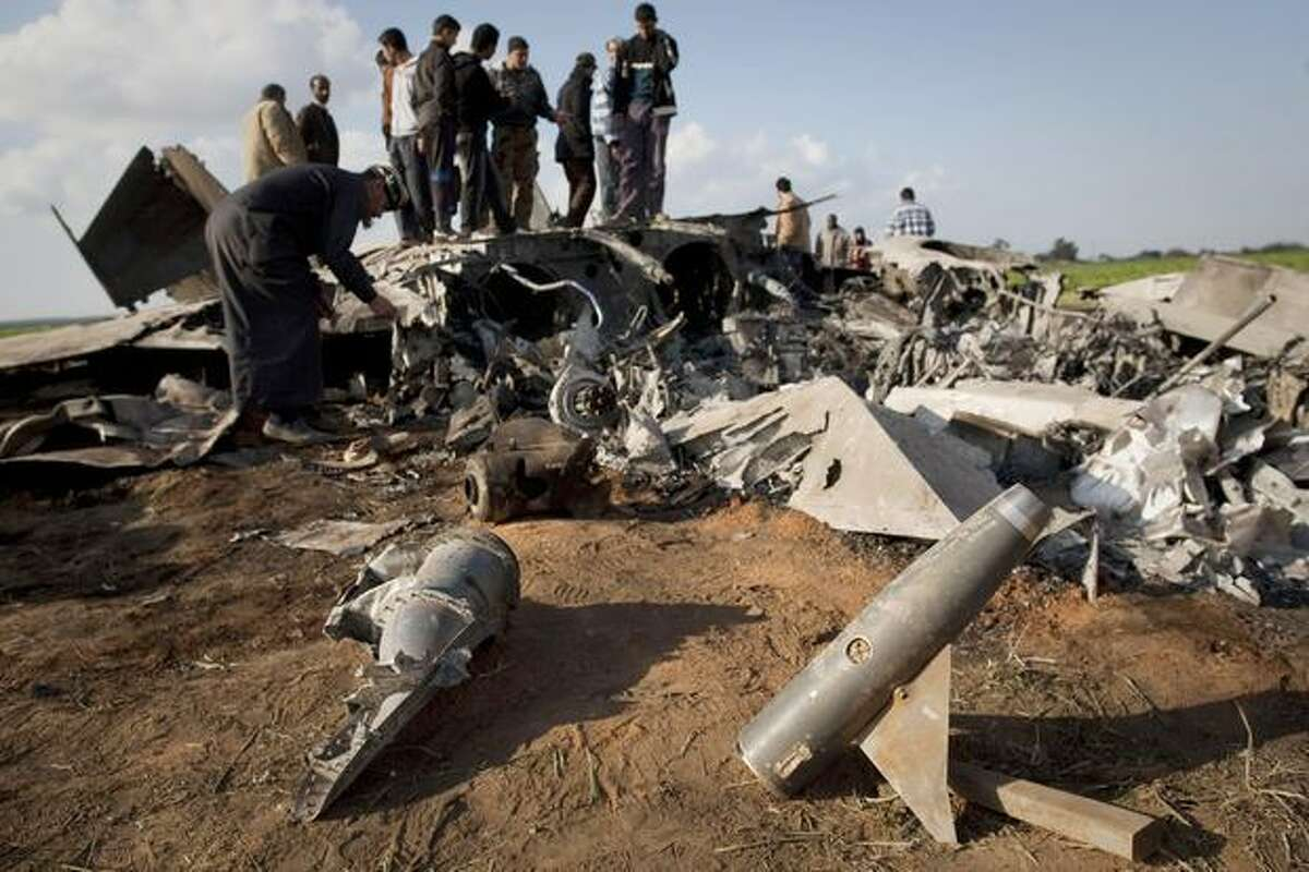 Libyans inspect the wreckage of a U.S. F-15 fighter jet after it crashed in an open field in the village of Bu Mariem, east of Benghazi, eastern Libya, on Tuesday with both crew ejecting safely. The U.S. Africa Command said both crew members were safe after what was believed to be a mechanical failure of the Air Force F-15. The aircraft, based out of Royal Air Force Lakenheath, England, was flying out of Italy's Aviano Air Base in support of Operation Odyssey Dawn.(AP Photo/Anja Niedringhaus)