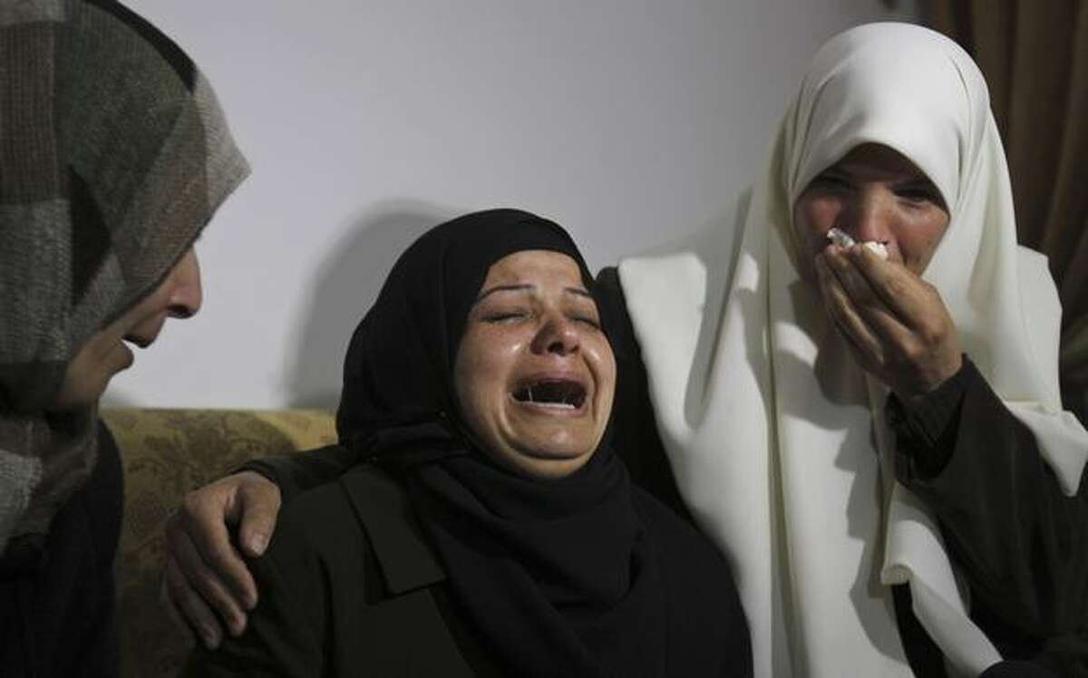 Palestinian relatives react during the funeral of the al-Helo family members killed in Israeli strikes on Gaza Tuesday, in Gaza City, Wednesday, March 23, 2011. Palestinian officials said an Israeli military strike killed four family members and four militants in the Gaza Strip on Tuesday after days of rocket fire toward Israel. Gaza militants barraged southern Israel with rockets and mortars Wednesday, drawing retaliatory Israeli airstrikes in an escalation of the gravest hostilities in the area since Israel went to war in the Palestinian territory two years ago. (AP Photo/Adel Hana)