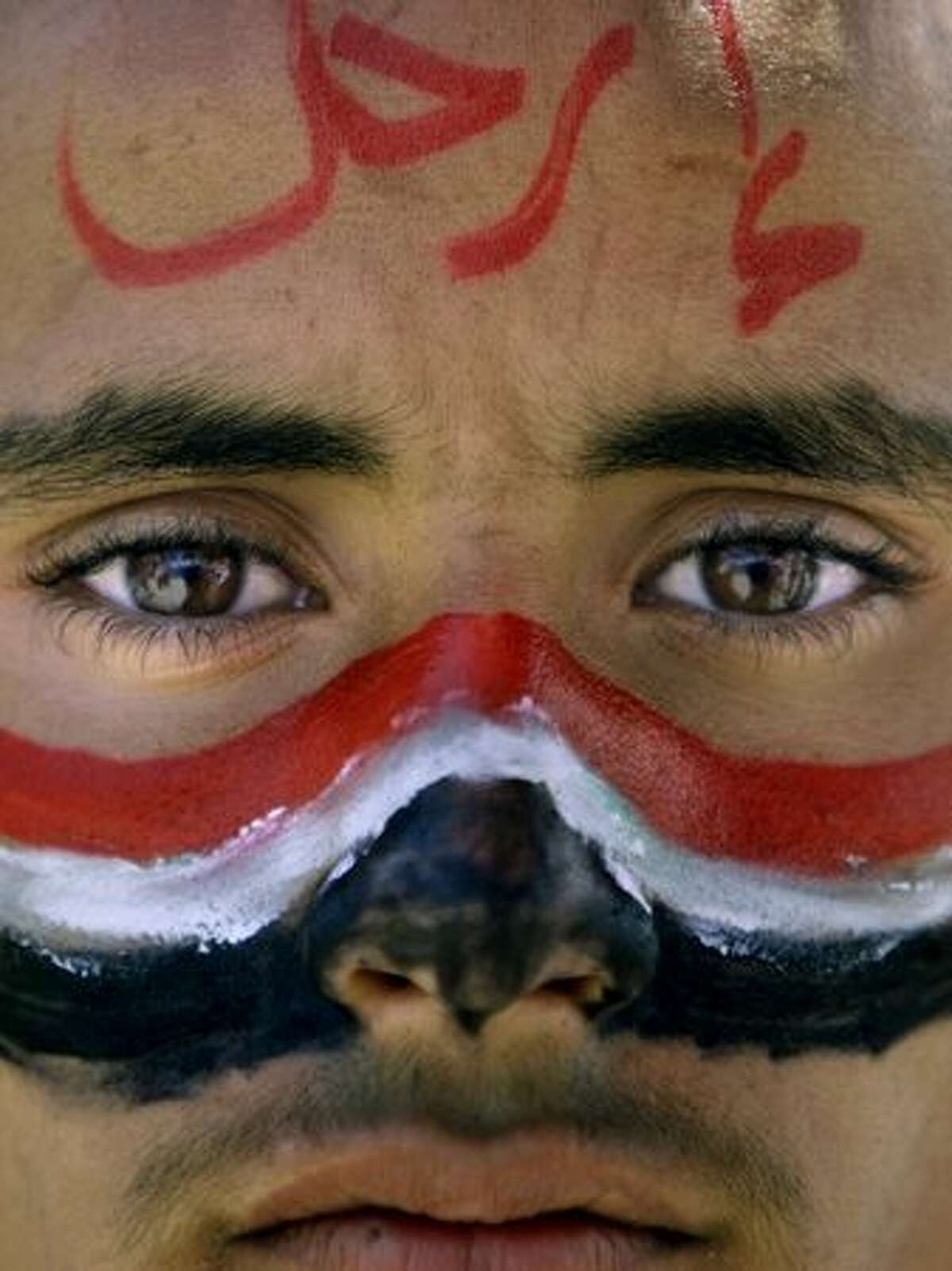 An anti-government protester with the colors of his national flag painted on his face during a demonstration demanding the resignation of Yemeni President Ali Abdullah Saleh, in Sanaa,Yemen, Thursday, March 24, 2011. His face reads,