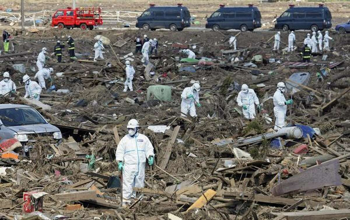 Tokyo Metro Police officers in protective suits search for missing residents at the site of a giant tsunami triggered by the March 11 earthquake in Minamisoma, Fukushima Prefecture, Japan, Monday, March 28, 2011. (AP Photo/Yomiuri Shimbun, Takuya Yoshino)