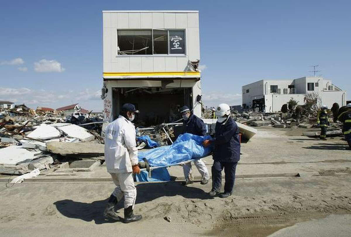 Recovery workers carry a body out of a tsunami-destroyed home in Natori, Miyagi Prefecture, northern Japan, Monday, March 28, 2011. The March 11 quake off Japan's northeast coast triggered the tsunami that barreled onshore and disabled the Fukushima Dai-ichi nuclear power plant. (AP Photo/Wally Santana)