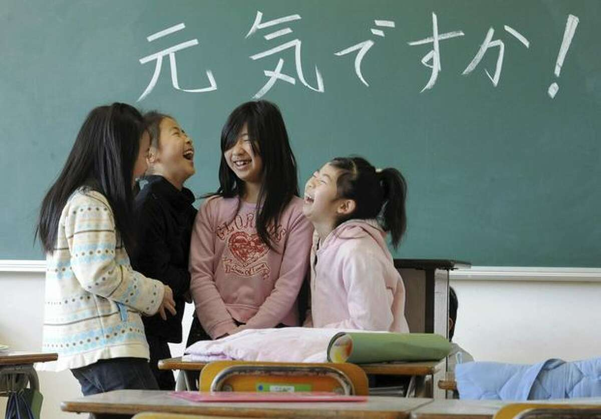 Elementary school children share a chuckle as they reunite for the first time since the March 11 earthquake at Masuda Nishi elementary school in Natori, Miyagi Prefecture, northern Japan, Monday, March 28, 2011. The words on the blackboard read