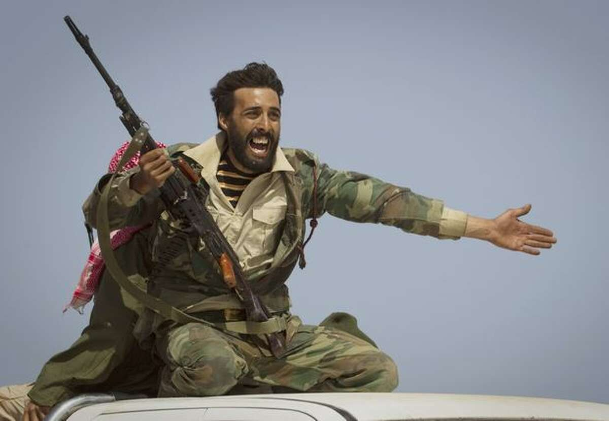 A Libyan rebel urges people to leave, as shelling from Gadhafi's forces started landing on the frontline outside of Bin Jawaad, 150 km east of Sirte, central Libya, Tuesday, March 29, 2011. (AP Photo/Anja Niedringhaus)