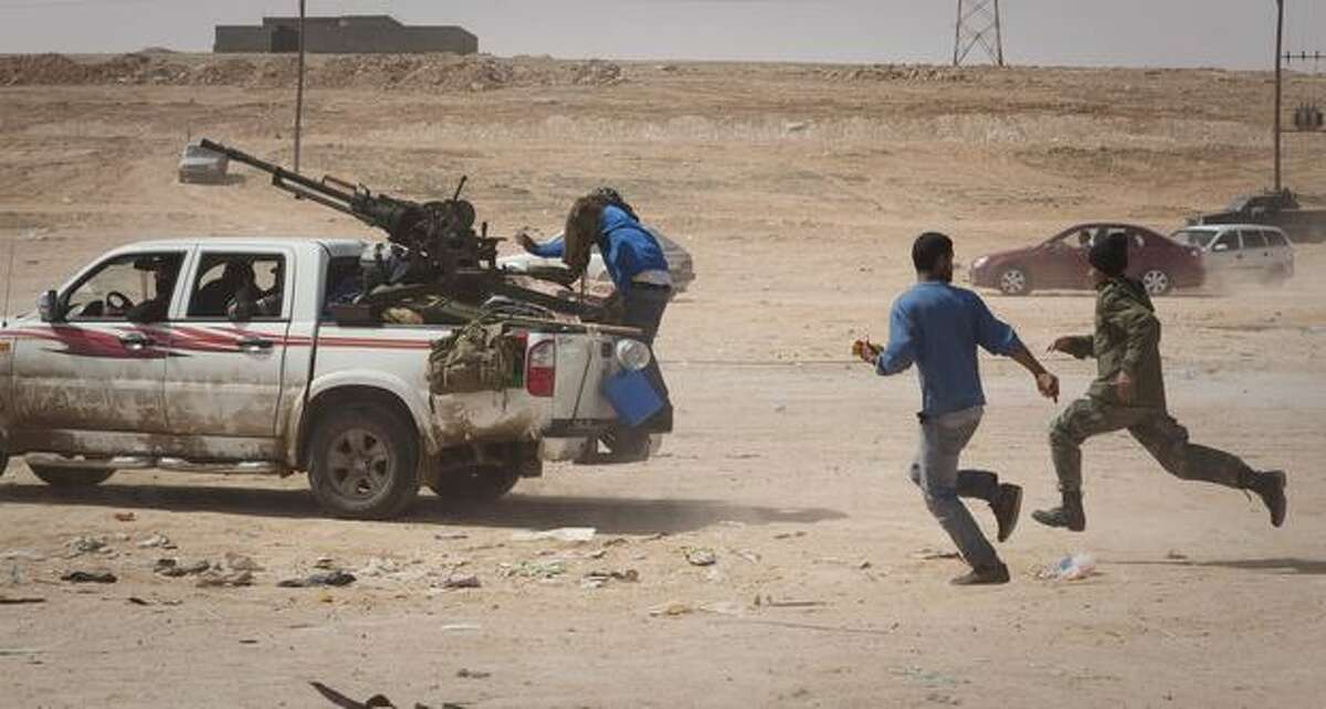 Libyan rebels flee as shelling from Gadhafi's forces start landing on the frontline outside of Bin Jawaad, 150 km east of Sirte, central Libya, Tuesday, March 29, 2011.(AP Photo/Anja Niedringhaus)