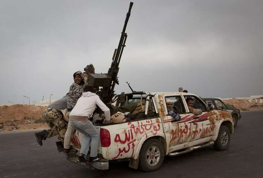 Libyan rebels jump onto the back of their vehicle as they leave Ras Lanouf, 250 km east of Sirte, central Libya, Tuesday, March 29, 2011. Gadhafi's forces drove the rebels out of Bin Jawwad, a hamlet east of Sirte, on Tuesday. Cars and trucks of the retreating rebels filled both lanes of the highway east to the oil port of Ras Lanouf. (AP Photo/Anja Niedringhaus)