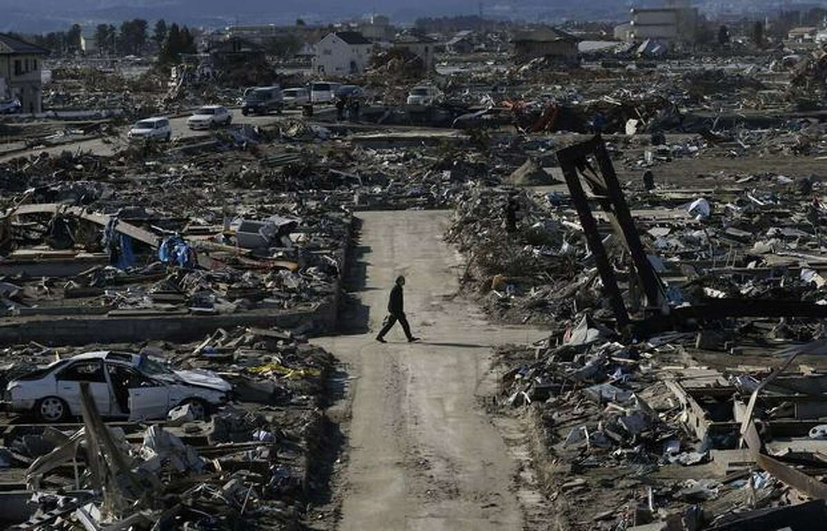 A man walks through the destroyed neighborhood below Weather Hill, Sunday, March 27, 2011, in Natori, Japan. The hill, a neighborhood centerpiece, was originally built to give fishermen a view of sea conditions but now offers an unforgettable look of the mass destruction left from tsunami caused by a magnitude 9.0 earthquake on March 11. (AP Photo/Wally Santana)
