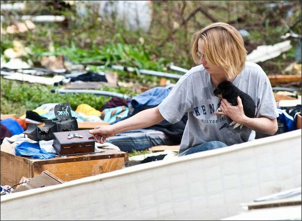 Robin Groves holds one of two newborn puppies recovered after a tornado destroyed the home of Bob Huggins in Mannington, Ky, on Friday as she looks for other salvageable items from the destruction. A Good Friday spring storm that moved through Kentucky spawned at least one confirmed tornado, and high winds and hail damaged homes, trees and power lines. (AP Photo/The Messenger, Jim Pearson)