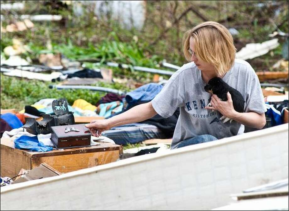 Robin Groves holds one of two newborn puppies recovered after a tornado destroyed the home of Bob Huggins in Mannington, Ky, on Friday as she looks for other salvageable items from the destruction. A Good Friday spring storm that moved through Kentucky spawned at least one confirmed tornado, and high winds and hail damaged homes, trees and power lines. (AP Photo/The Messenger, Jim Pearson) Photo: Ava Gerlitz / Ava Gerlitz