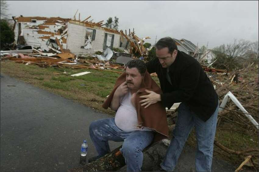 Deputy Randy Morrow puts a blanket on Jeff Carman, whose Penny Lane house was destroyed by a tornado, Friday, in Murfreesboro, Tenn. (AP Photo/The Tennessean, Aaron Thompson)
