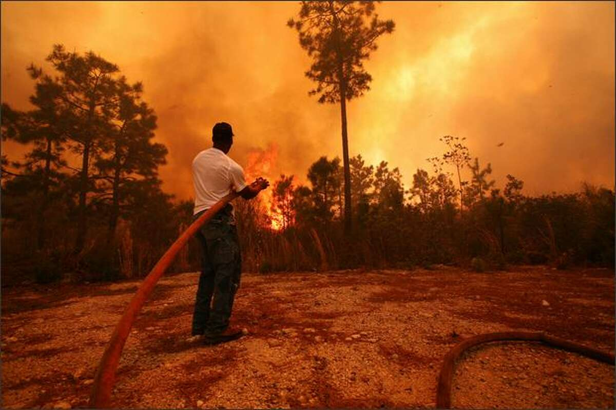A man sprays water on a raging fire as it threatens nearby homes near Conway, South Carolina. South Carolina Gov. Mark Sanford declared a state of emergency Thursday for a coastal county where a wildfire has consumed thousands of acres and destroyed dozens of homes.