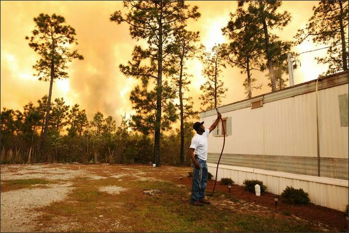 Scott Vereen sprays water on his family's home as a wildfire rages near Conway, South Carolina. South Carolina Gov. Mark Sanford declared a state of emergency Thursday for a coastal county where a wildfire has consumed thousands of acres and destroyed dozens of homes.
