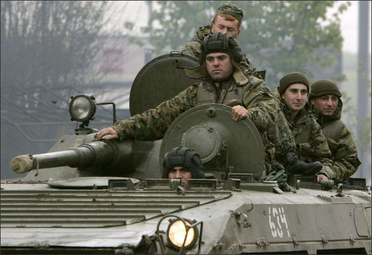 Georgian soldiers leave the Mukhrovani army base after putting down a mutiny, east of Tbilisi. Georgia put down a mutiny at a military base on Tuesday and accused Russia of financing a coup to stir up trouble on the eve of NATO war games in the ex-Soviet republic.