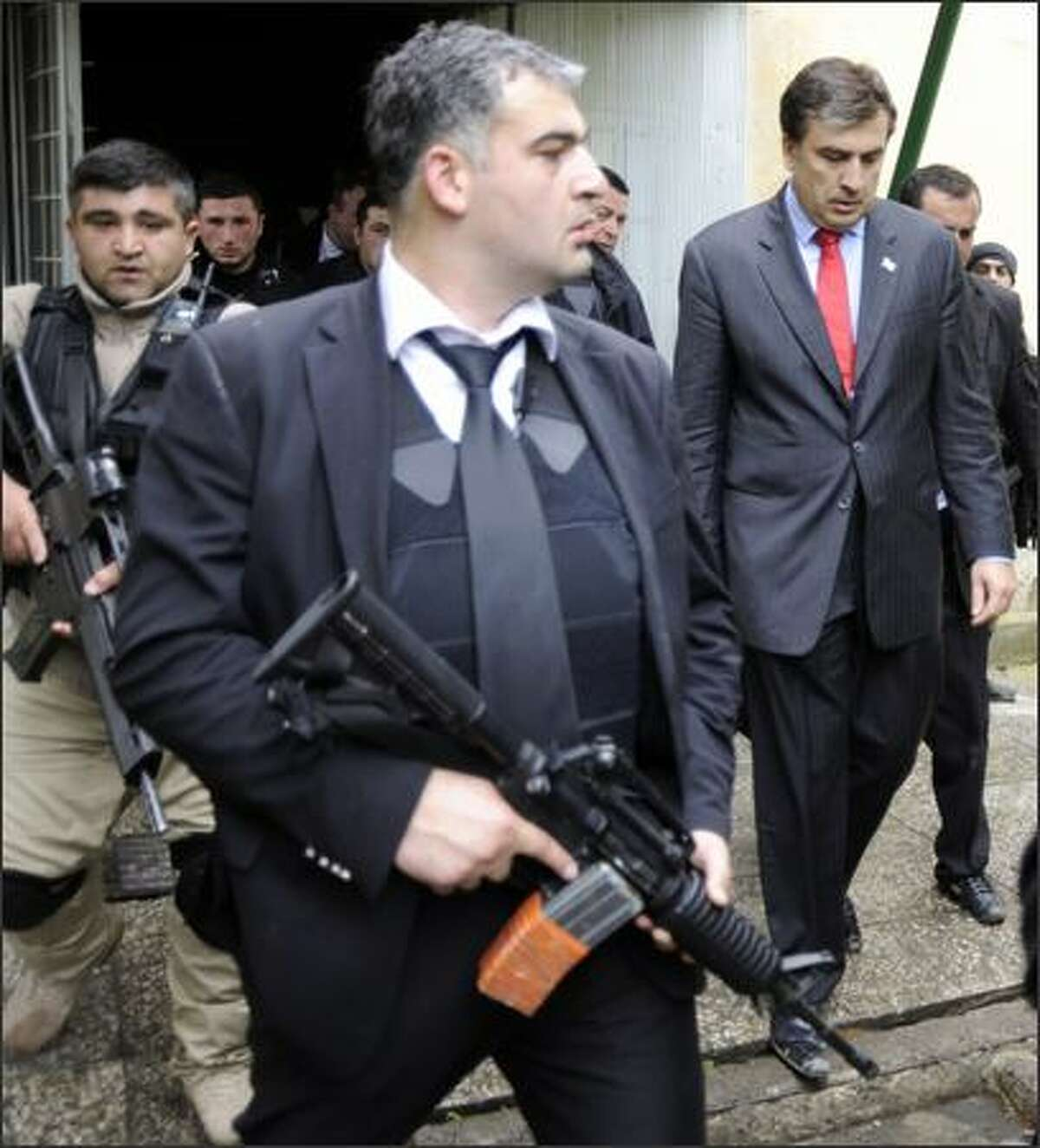 Georgian President Mikheil Saakashvili (R), surrounded by his guards, enters the Mukhrovani military base where some soldiers staged a mutiny, six miles east of Tbilisi. Georgia put down a mutiny at a military base on Tuesday and accused Russia of financing a coup to stir up trouble on the eve of NATO war games in the ex-Soviet republic.
