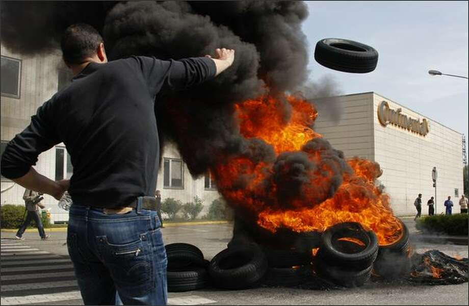 An employee from the Continental tire company throws a tire onto a bonfire during a demonstration at the Continental plant in Sarreguemines, eastern France. Continental announced in March that it will cut nearly 2,000 jobs and close production at two high-cost European manufacturing sites amid a severe crisis in the auto industry. REUTERS/Vincent Kessler Photo: Reuters / Reuters