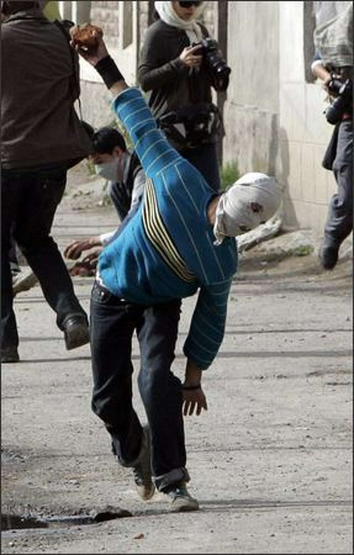 A protester throws a stone toward Indian policemen during an anti-election protest in Srinagar. Kashmir's separatist leaders are struggling to win back popular support, and are hoping that a boycott of Thursday's election to the Indian parliament may yet breathe new life into the 20-year movement. REUTERS/Danish Ismail