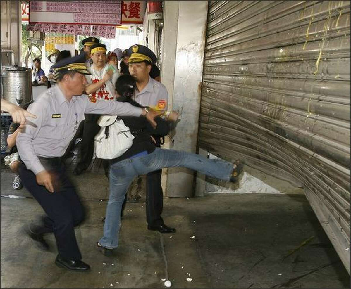 A policeman holds back a woman from kicking the shutters of a bank during a street protest in Taipei against Taiwanese banks linked with Lehman Bros. Around 1,000 investors who suffered losses from their Lehman-linked investments joined forces with Hong Kong investors on Friday to request that the government help them seek a full reimbursement from associated banks. REUTERS/Nicky Loh