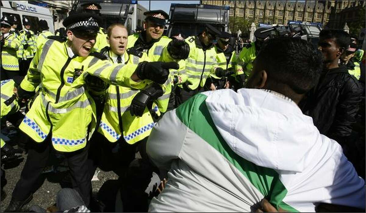 Police officers shout at pro-Tamil demonstrators during a protest in Parliament Square in London. REUTERS/Stefan Wermuth