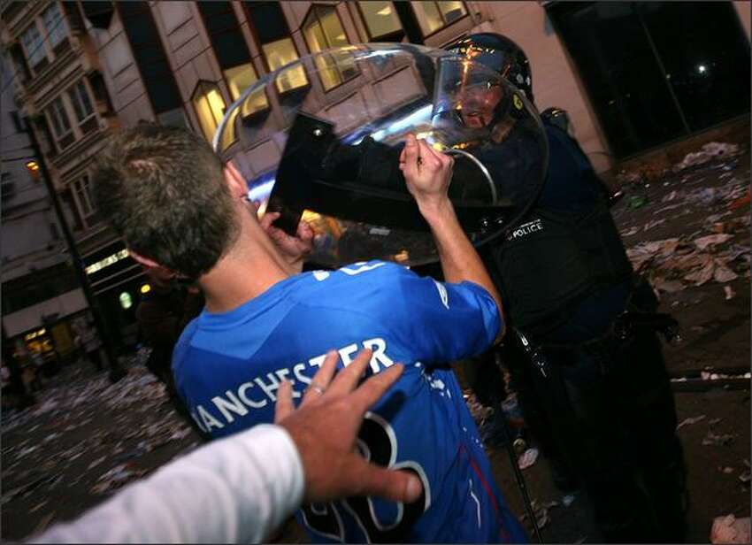 Injured Rangers fans are confronted by riot police in Manchester, England.