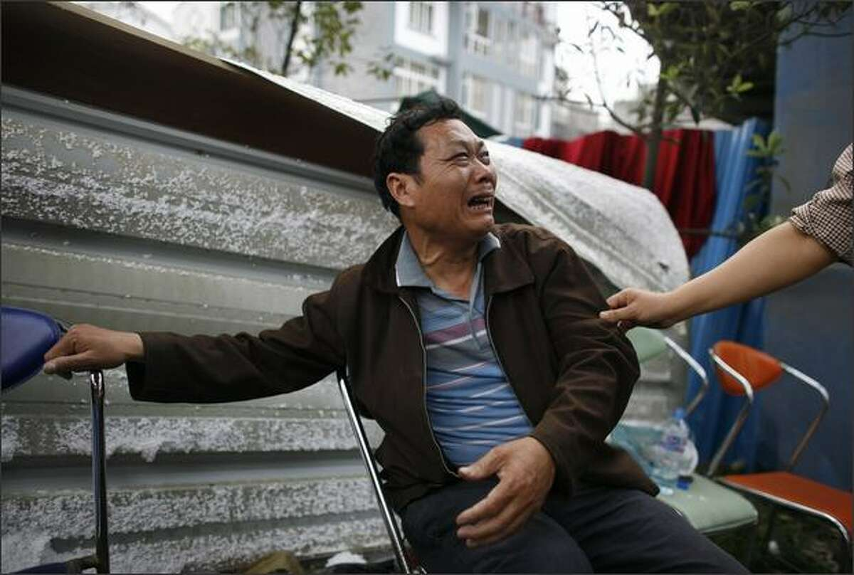 A grieving parent cries outside a school after identifying his child who was killed in by the powerful earthquake in DuJiangyan, China. The death toll has already risen to nearly 15,000 and is expected to rise with 25,000 still missing. A large dam near the hard-hit city of Dujiangyan, the Zi Ping Pu dam, has been damaged by the quake, causing serious cracks; some 2,000 troops have been sent to plug the cracks.