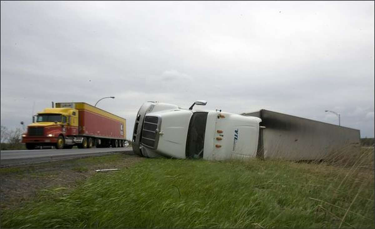 An overturned truck lies on Highway 20 eastbound on the outskirts of Montreal, Canada. Extreme high winds caused a number of trucks to overturn on the South Shore of Montreal. REUTERS/Christinne Muschi