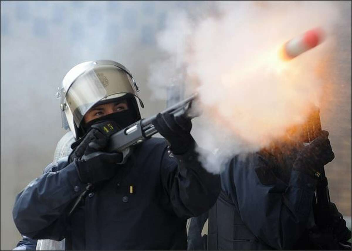Spanish riot police fire tear gas toward the building of the private shipbuilding company Naval Gijon during a protest by former shipyard workers who were forced into early retirement. The protesters have occupied the shipyard's buildings demanding assurances of their salaries after the company closes May 31. REUTERS/Eloy Alonso