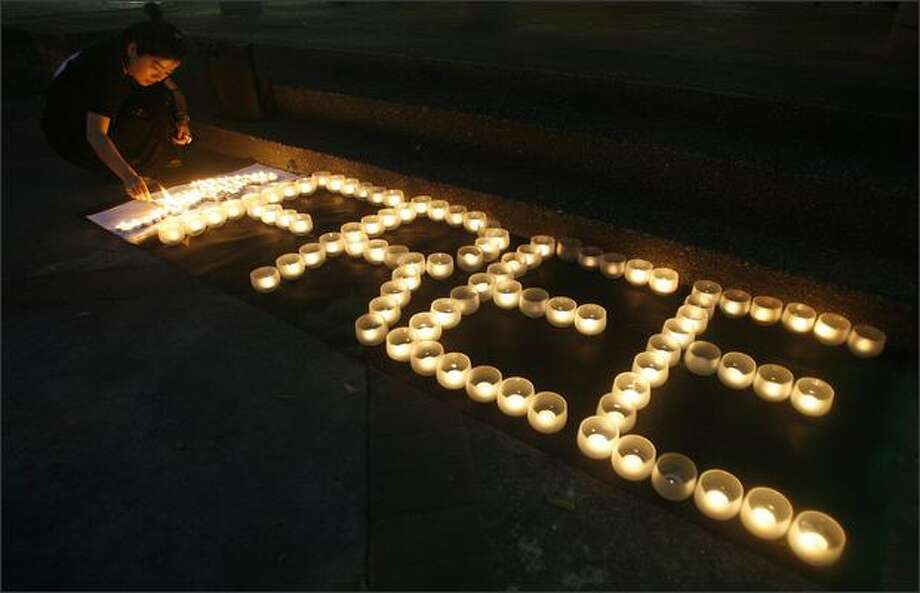 An activist lights a candle during a vigil in Taipei, Taiwan, in support of Myanmar opposition leader Aung San Suu Kyi. She went on trial on Monday and faces a further five years in detention, sparking threats of tougher international sanctions against the military regime. REUTERS/Nicky Loh Photo: Reuters / Reuters