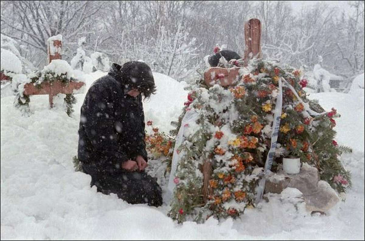 A woman mourns at the grave of one of the people who died in a crossfire between the army, backed up by armed civilians, and pro-Ceausescu supporters in Bucharest on Dec. 28, 1989. This year Romania celebrates 20 years since the violent uprising, during which the country's communist dictator, Nicolae Ceausescu, was toppled and shot on Christmas Day 1989. REUTERS/Charles Platiau