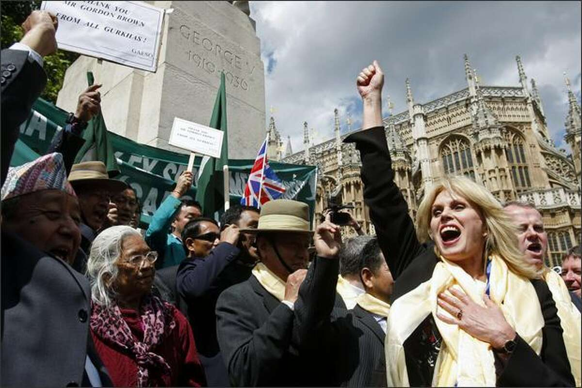 British actress and Gurkha rights campaigner Joanna Lumley, right, Gurkha veterans and supporters, react, outside the Houses of Parliament, in London, Thursday. The government announced Thursday that it will allow retired Gurkha veterans to settle in the country. (AP Photo/Sang Tan)