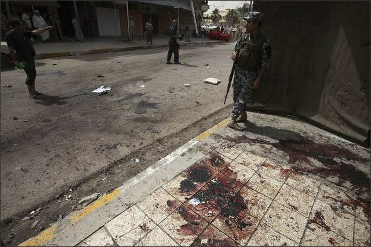 An Iraqi policeman stands on a blood stained sidewalk where three US soldiers and four Iraqis were killed in a blast in Dora neighborhood in Baghdad, Iraq, Thursday. Three American soldiers were killed and nine others wounded in this attack in Baghdad, the U.S. military said. (AP Photo/Karim Kadim)