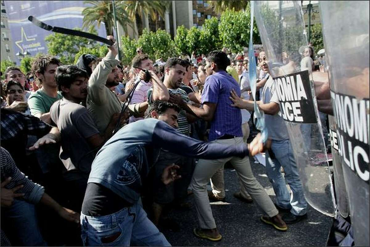 Muslim immigrants clash with riot police in Athens, Greece, after a policeman allegedly took a man's Quran and tore it up while checking his identity papers.