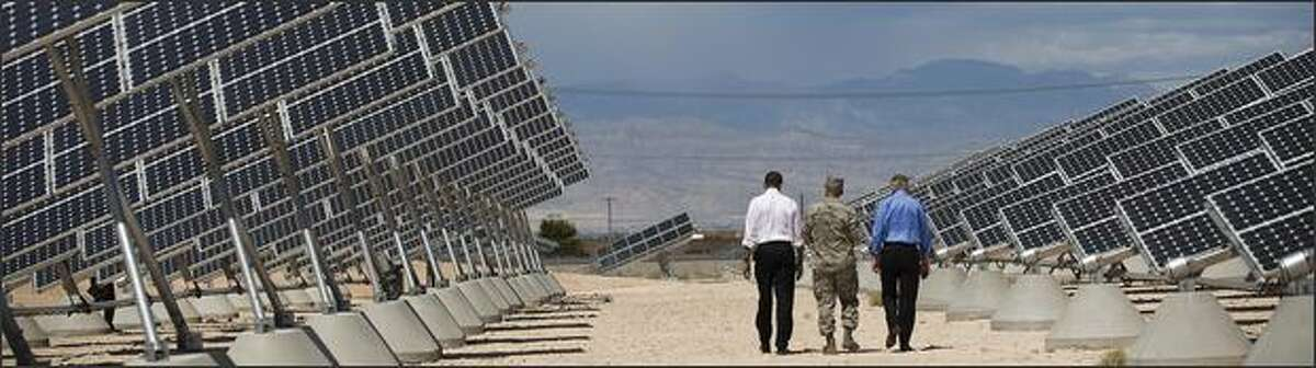 President Barack Obama, left, and Senate Majority Leader Harry Reid, right, tour the photovoltaic array at Nellis Air Force Base in Las Vegas, Nev., with base commander Col. Howard Belote.