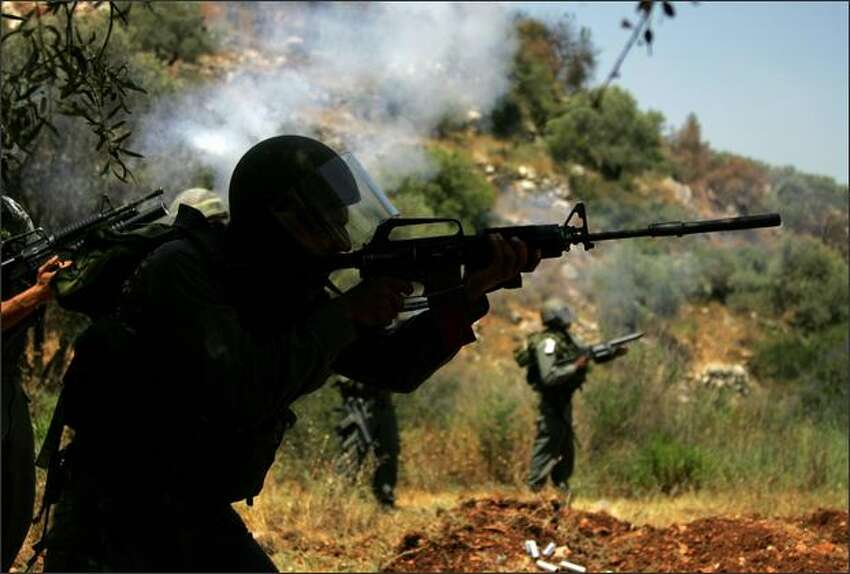 Israeli troops fire teargas and rubber bullets at Palestinian demonstrators (not seen) during a protest against the construction of Israel's controversial separation barrier in the West Bank village of Nilin. Israel says the barrier, which would eventually reach 400 miles, aims at stopping