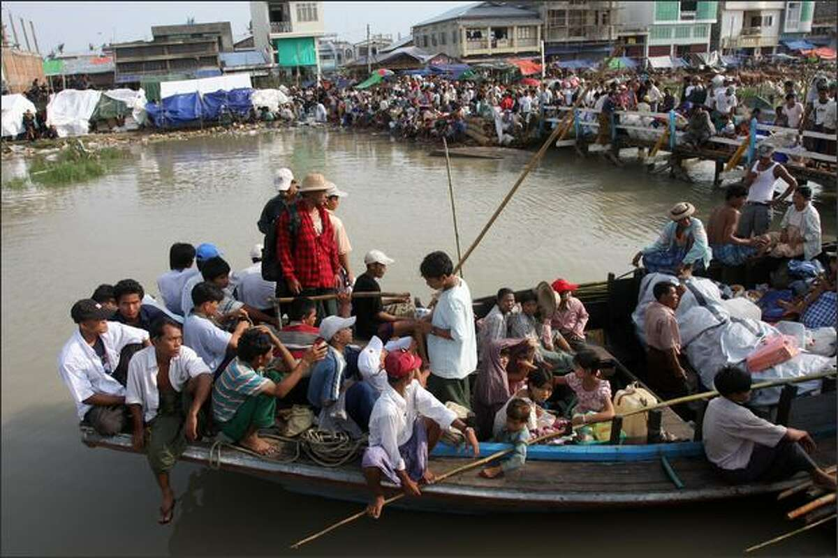 People affected by cyclone Nargis wait to board boats prior to travel back to their devastated villages in the southwest Irrawaddy Delta in the town of Labutta. Myanmar denied any delays to cyclone aid, but the United Nations said the operation to help 2.4 million survivors is still moving too slowly a month after the deadly storm. Cyclone Nargis left 133,000 people dead or missing when it plowed across Myanmar one month ago, laying waste to vital farmlands and wiping villages off the map.