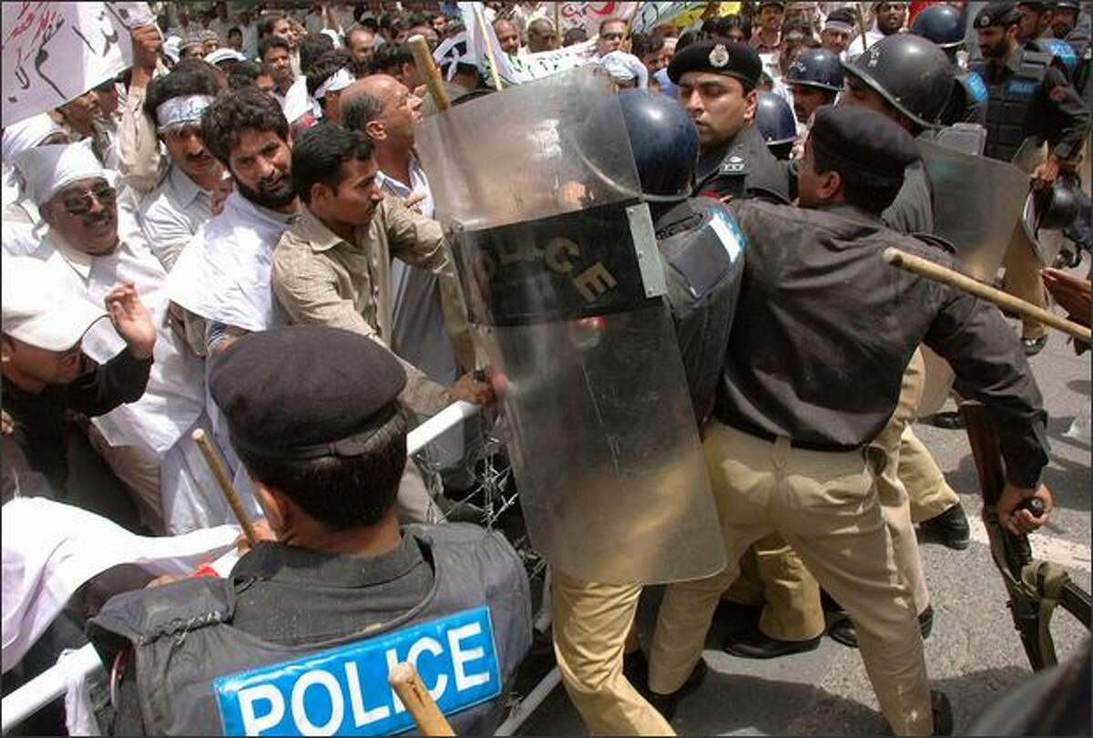 Pakistani police scuffle with government employees during a protest rally in Lahore to denounce soaring price hikes in the country. Pakistan raised interest rates on May 22 in a bid to curb soaring inflation. Average inflation may be 11 percent this year, double the target of 6.5 percent for the past fiscal year.