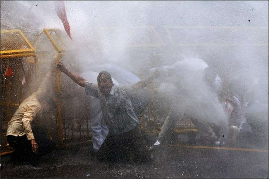 Indian police officials use a water cannon to disperse activists from India's main opposition Bharatiya Janata Party (BJP) during a protest against the Congress-led UPA government's hike on petroleum products in New Delhi. The Indian government hiked fuel prices to stem huge losses at state oil firms caused by surging crude costs, with petrol up by around 11 percent and diesel up by 9.4 percent. Photo: Getty Images / Getty Images