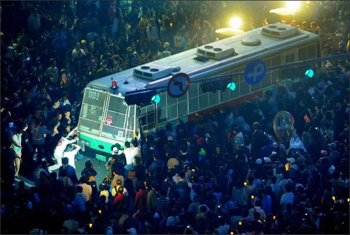 South Korean protesters tug police buses as police block them during a rally against US beef imports in Seoul. All the top aides of South Korean President Lee Myung-Bak have offered to resign to shoulder the blame for a political crisis over US beef imports, the president's office said.