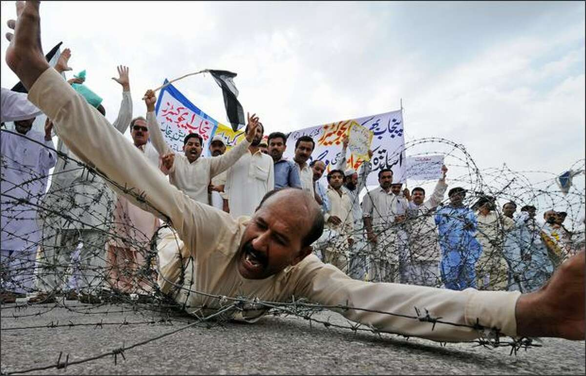 Pakistani government schools teachers shout slogans as they try to cross barbed wire during a demonstration in front of the Parliament House in Islamabad on Monday to protest against the government for increasing fuel, food prices and low salaries. Anger is mounting among the country's 160 million people over shortages of food and other commodities, coupled with frequent power outages, factors that contributed to the defeat of Musharraf's backers. The new government has said that economic targets cannot be met because the previous administration