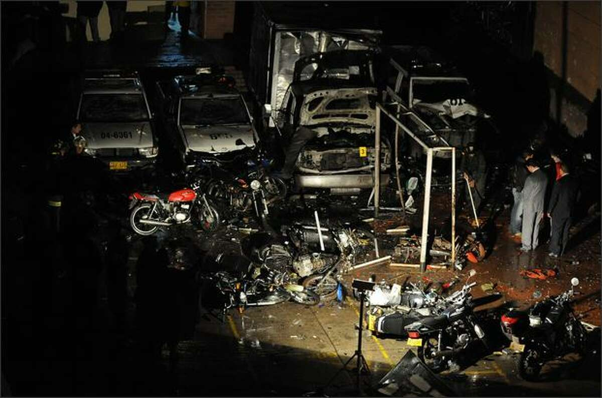 Members of the Colombian Police inspect the damage caused after two missiles explode at police headquarters in the Suba locality, Bogota, on Tuesday. The explosions left 13 injured.