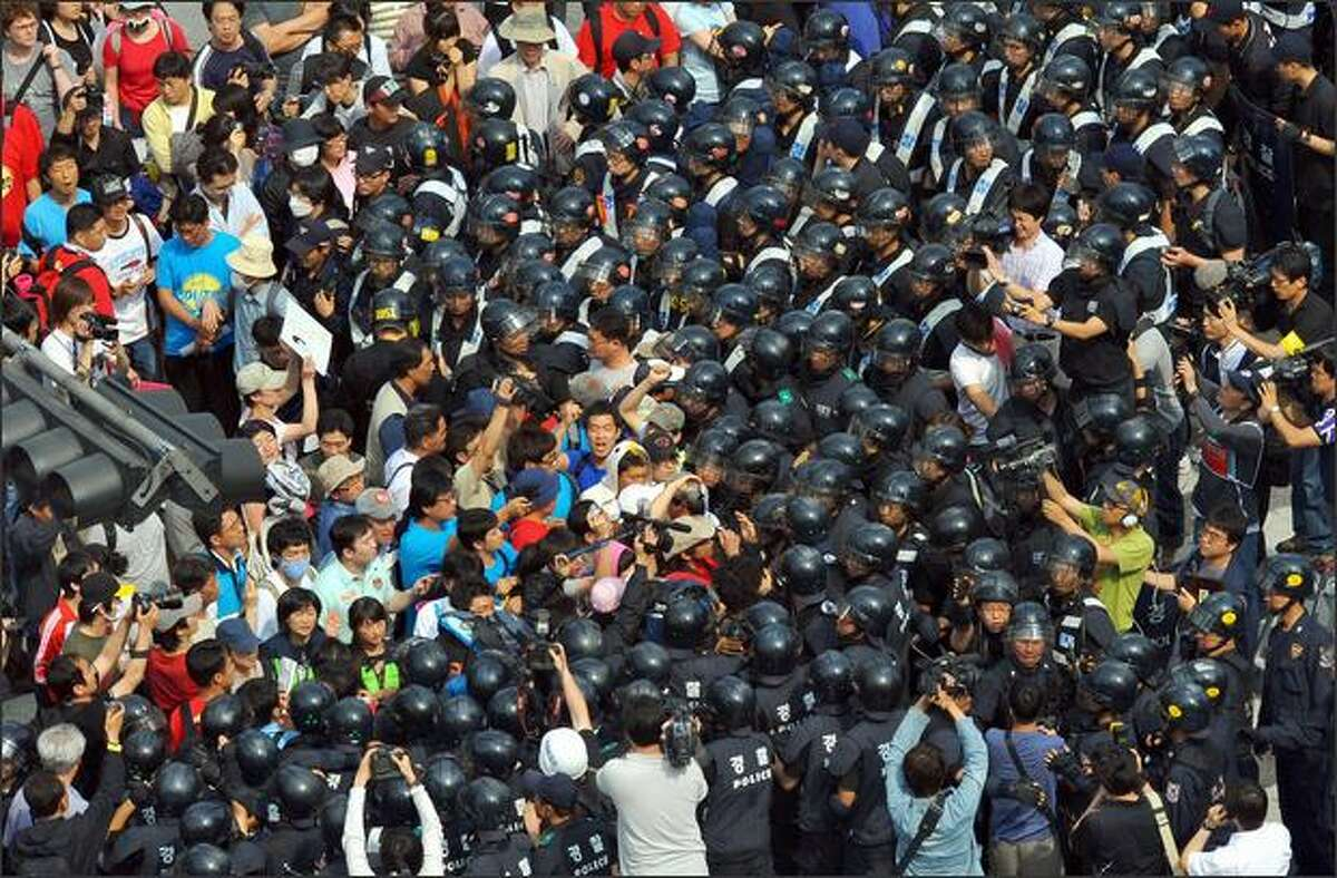Police push South Korean protesters to the sidewalk after an overnight rally against US beef imports in Seoul on Wednesday. Tens of thousands of South Korean protesters staged a candlelight rally overnight demanding the scrapping of an agreement to resume US beef imports and the resignation of President Lee Myung-Bak.