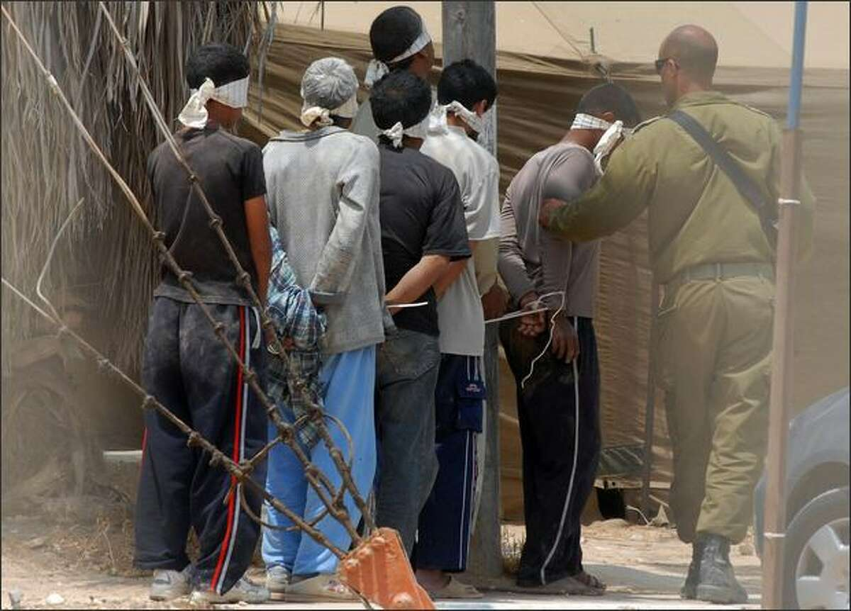 Blindfolded detainees are led by Israeli soldiers at a military base located near the northern Gaza Strip after he was detained during a military operation in the territory, on Wednesday. Israel said today it supported an Egyptian-mediated proposal for a truce in and around the Hamas-ruled Gaza Strip but instructed the military to continue preparing for an offensive.